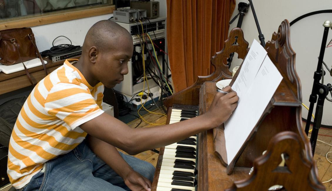 Boy editing lyrics at piano (photo: Miriam Douglas)