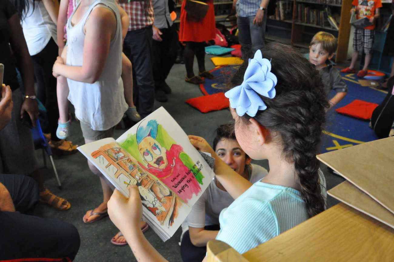 Child reading aloud from her picturebook