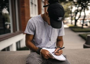 A young writer sits outside with a pen and notepage